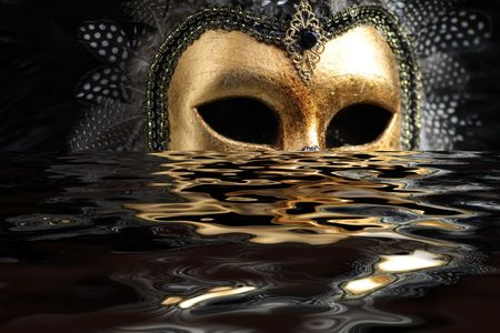Venetian mask decorated with gold leaf and embedded with fowl feathers with reflection on water. photo