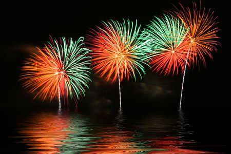 holiday lights display: Bright and colorful fireworks display with reflection on water. Stock Photo