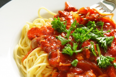 Freshly cooked plate of spaghetti with seafood sauce sprinkled with fresh green herbs. photo