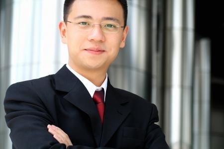 confianza: Bueno buscando asian hombre de negocios de pie, con los brazos doblados.