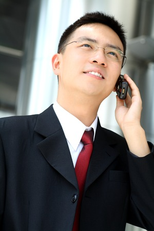 Good looking asian business man talking into a hand phone. Stock Photo