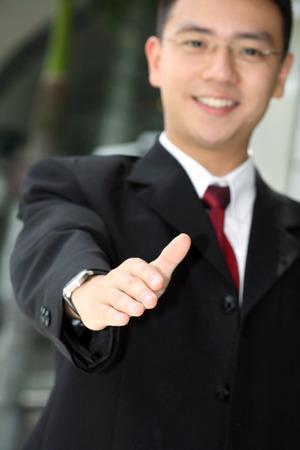 porgere: Good looking asiatiche uomo d'affari in piedi con le braccia aperte pronta a stringere la mano.
