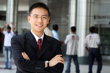 Good looking asian business man standing with arms folded. photo