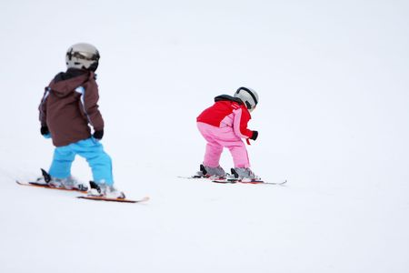 Winter scene with two kids skiing down a slope. Stock Photo