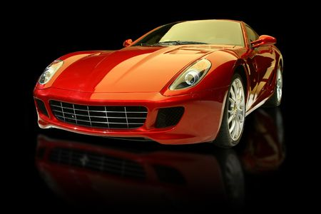 Red luxury sports car against a black background and with reflection.