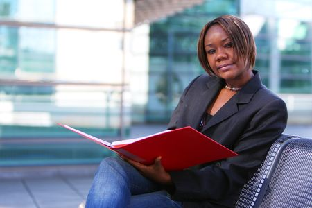 African american woman holding documents in an office environment. photo