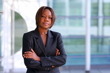 African american woman standing with arms folded in an office environment. Stock Photo