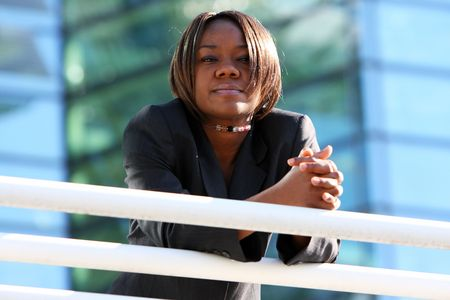 african education: African american woman standing with arms folded in an office environment. Stock Photo