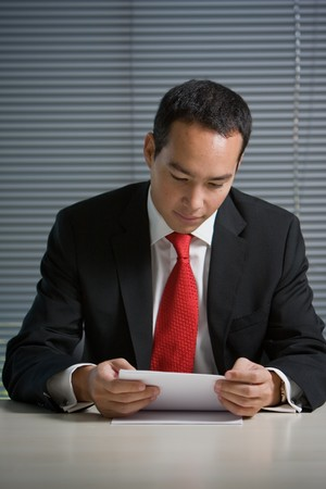 Good looking caucasian asian business man browsing and reading documents
