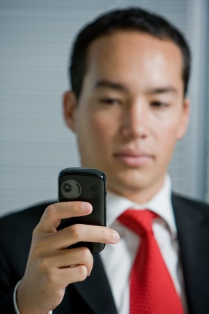 Business man holding a mobile or cell phone photo