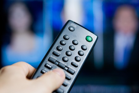 Hand holding a remote control pointing to a blurred TV program Stock Photo