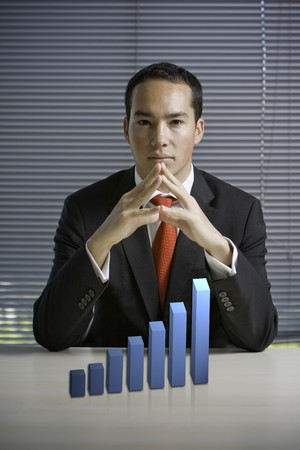 raise: Asian business man with a 3D growth graph or chart showing increase Stock Photo