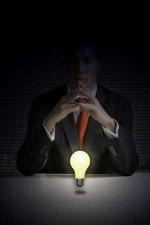 Asian business man with a floating light bulb glowing in the dark, energy conservation theme photo