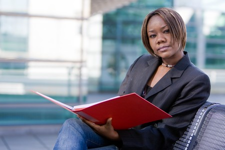 African american business woman reading documents in a folder in front of an office building Stock Photo