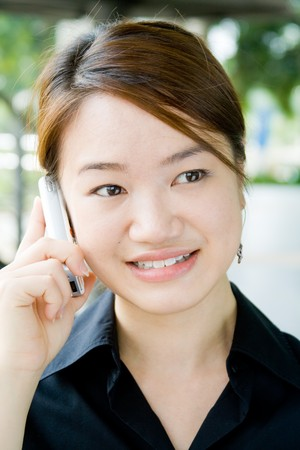 Beautiful and pretty asian business woman posing with mobile phone photo