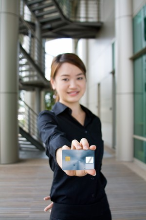 Beautiful and cute asian business woman presenting credit card for purchase photo