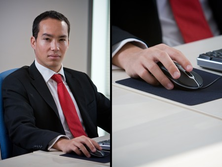 Handsome asian chinese business man using computer holding the mouse photo