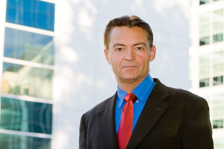 Successful caucasian business man, mature looking, posing in front of a office area outdoors