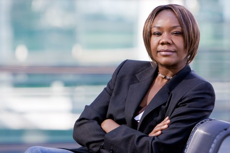 Black african american business woman posing in front of a modern office building with arms folded Stock Photo