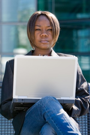 African american business woman with a computer notebook browsing outside an office building photo