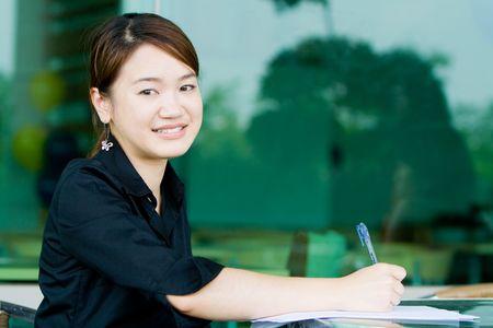Joven mujer de negocios asiáticos de trabajo y por escrito su informe en un entorno de oficina Foto de archivo - 5171171