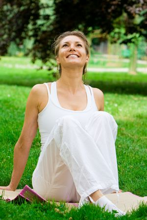 breath: Blonde girl in nature green park exercising yoga, fitness program Stock Photo