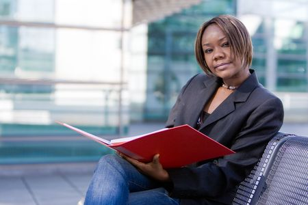 African american business woman reading documents in a folder in front of an office building photo