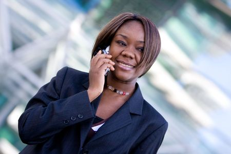 African american business woman talking on a mobile cell phone in front of an office building photo