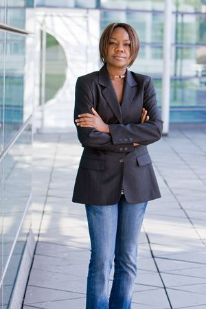 Black african american business woman posing in front of a modern office building with arms folded photo