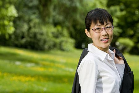 Environmentally friendly asian business woman outdoors in nature with green grass photo