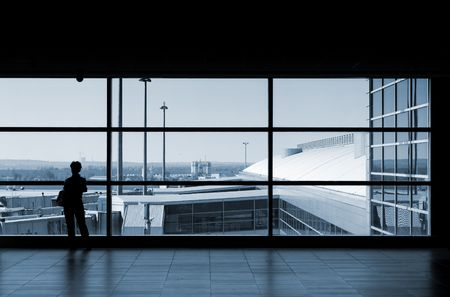 Airport lounge or waiting area with business man standing looking outside of window towards control tower photo
