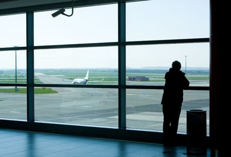 control tower: Airport lounge or waiting area with business man standing looking outside of window towards control tower Stock Photo