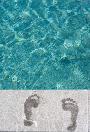 Footprints with turqoise blue swimming pool at vacation resort Stock Photo