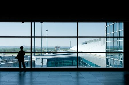 Airport lounge or waiting area with business man standing looking outside of window towards control tower Editorial