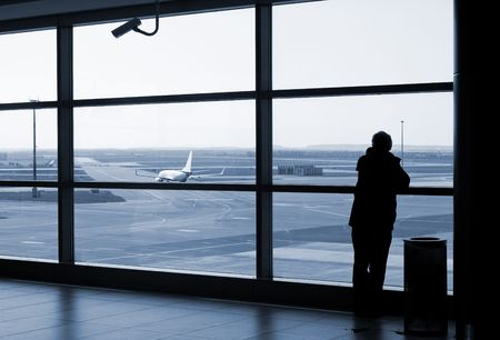 working area: Airport lounge or waiting area with business man standing looking outside of window towards control tower Editorial