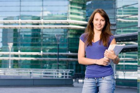 Pretty attractive caucasian white girl standing outside modern college school with books