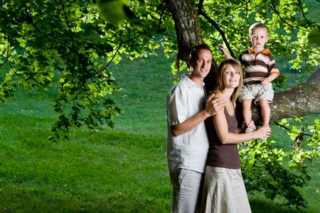 Happy perfect young family with dad, mom and son outdoors having fun Stock Photo