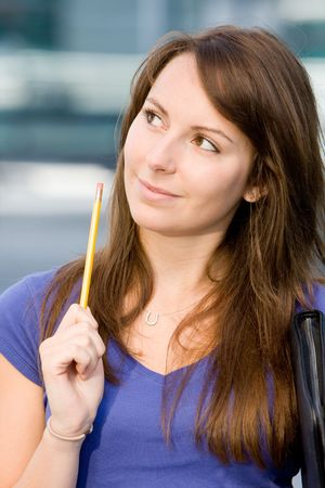 Pretty beautiful caucasian white girl pondering or thinking outside college school holding pencil photo