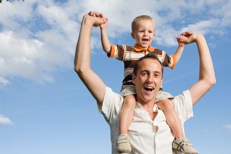 shoulder ride: Padre llevando a su hijo en la espalda piggy paseo al aire libre contra el cielo azul y naturaleza Foto de archivo