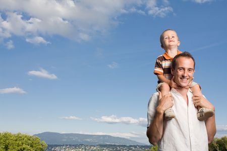 shoulder ride: Father carrying his son on piggy back ride outdoors against nature and blue sky Stock Photo