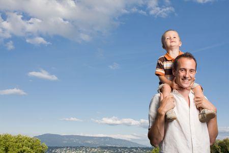 shoulder ride: Padre llevar a su hijo en Piggy Back paseo al aire libre contra la naturaleza y el azul del cielo