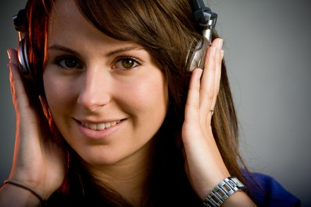 Beautiful brunette teenage model in a night club listening to music headphones photo