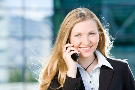 Blonde business woman in front of office building talking on cell mobile phone photo