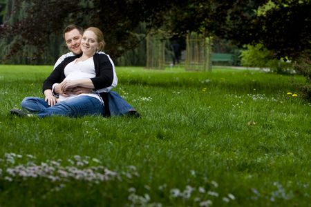 Husband and wife maternity expecting a child or baby posing in the park photo