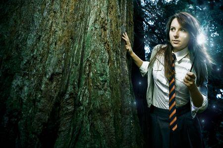 Chica adolescente asistente con los hechizos de la fundición de varita mágica en un bosque encantado de fantasía Foto de archivo - 6811572