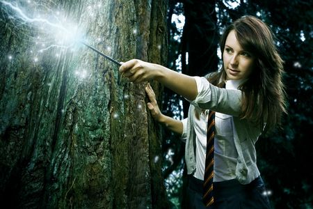 Chica adolescente asistente con los hechizos de la fundición de varita mágica en un bosque encantado de fantasía Foto de archivo - 6811578