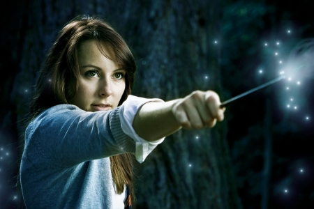 Teenage wizard girl with magic wand casting spells in a enchanted fantasy forest photo