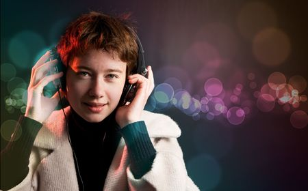 Pretty woman deejay enjoying music on dance floor with colorful bokeh background photo