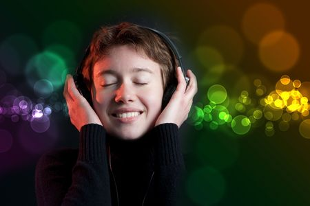 Pretty woman deejay enjoying music on dance floor with colorful bokeh background Stock Photo - 6811586