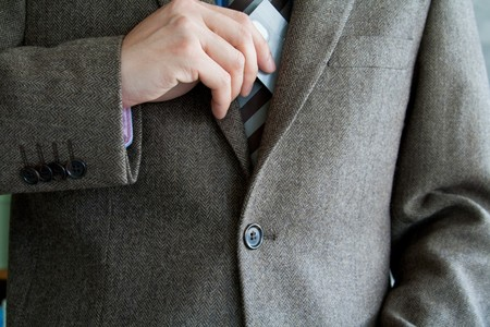Business man holding or taking out his credit card from his formal suit jacket